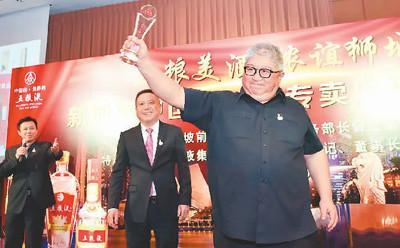 中国侨网图为云伟龙被中国某名酒公司授予最佳代理商奖杯。   资料图片
