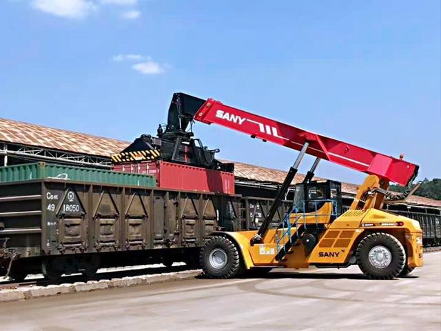 """说明: 装卸车正在往""""玉林—北部湾港""""海铁联运班列装载货物。"""