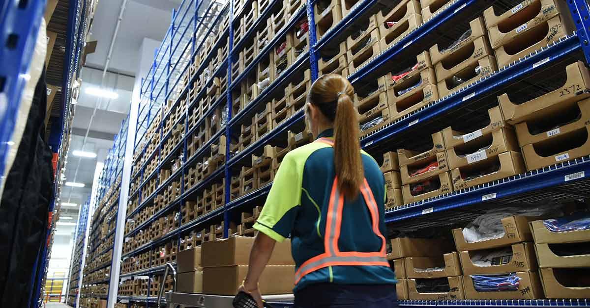 说明: An employee picks up orders from shelves in a warehouse at SingPost Regional eCommerce Logistics Hub in Singapore.